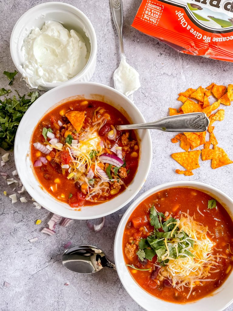 Two bowls of hearty turkey chili with sour cream, cheese, cilantro, and nacho cheese chips.