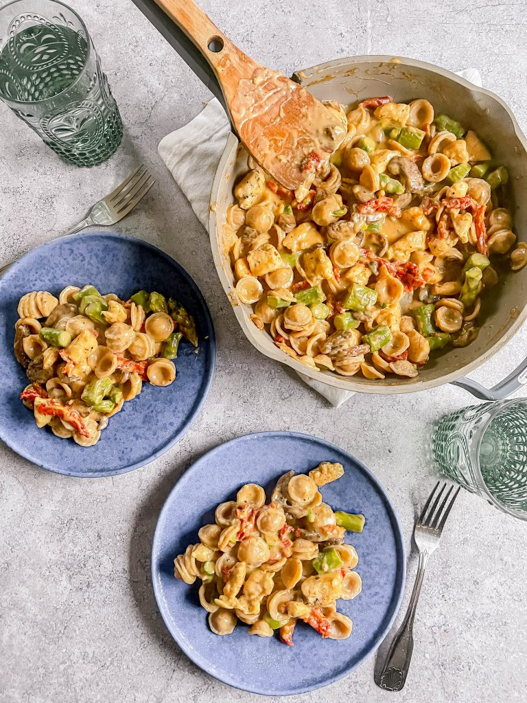 A large skillet full of orecchiette, mushrooms, asparagus, sun-dried tomatoes, chicken, all in a creamy sauce.   Two blue plates with pasta and two green cups, two silver forks.