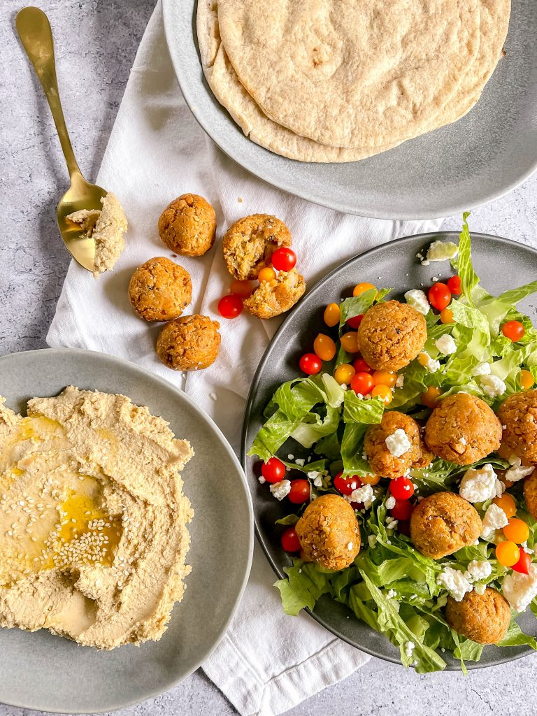 Three gray plates: one in the center right with falafel balls over salad, one to the left with hummus, one to the upper right with a stack of pitas. Gold spoon, cherry tomatoes scattered.