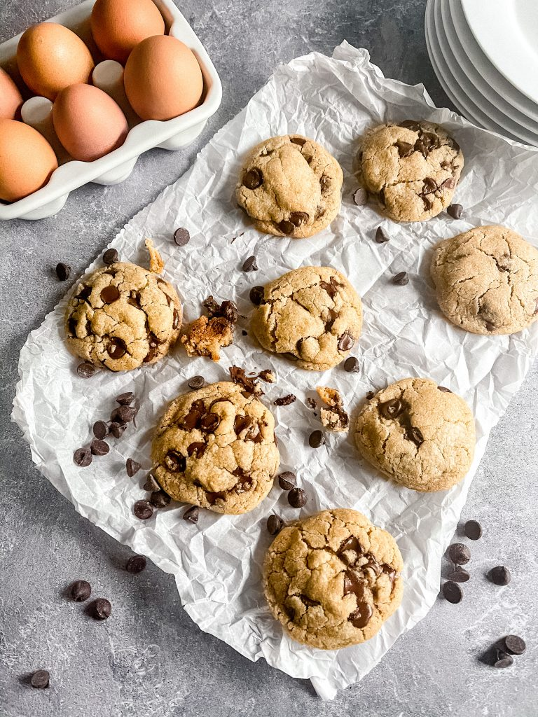 Eight chocolate chip cookies ontop of some parchment paper with chocolate chips all around them. A carton with six eggs to the left, and a stack of white plates in the upper right corner.