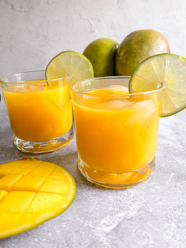 Two vibrant, orange margaritas in front of a carton of green mangos.