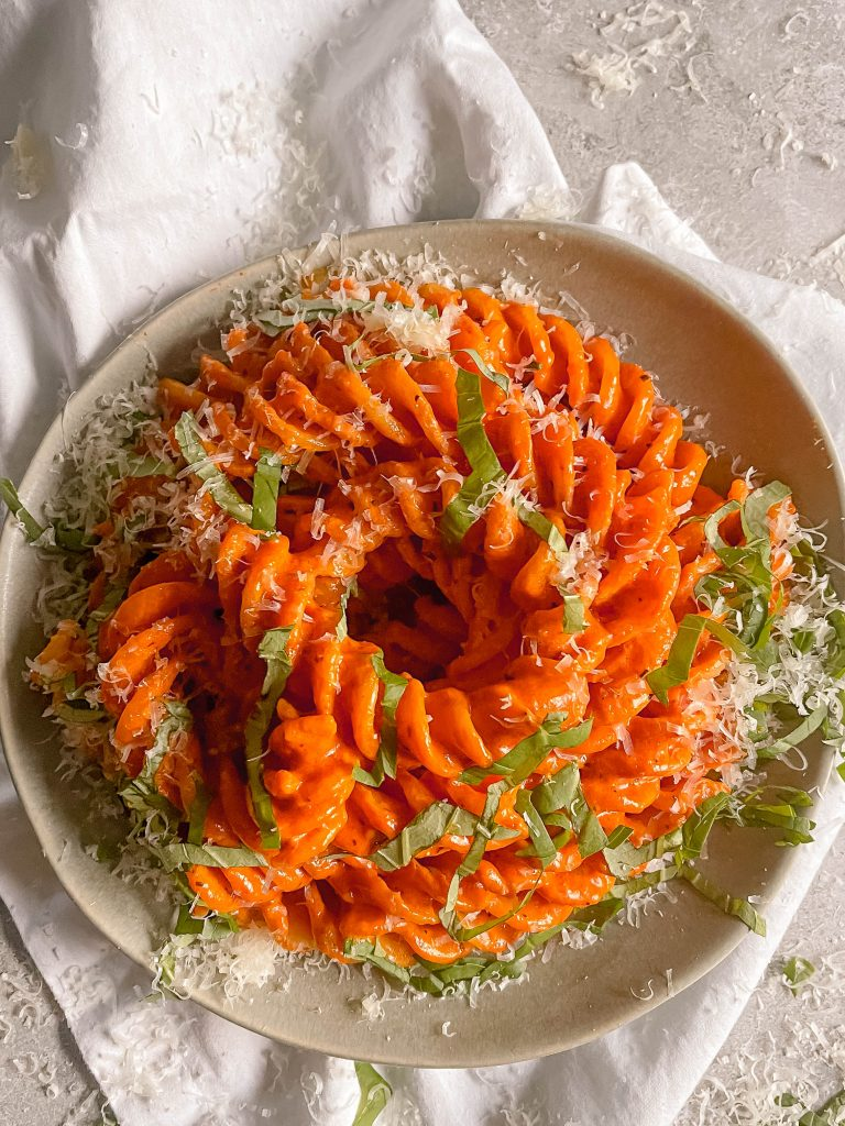A bowl with bright orangey-red tequila sauce-soaked noodles. Chopped basil and parmesan ontop.