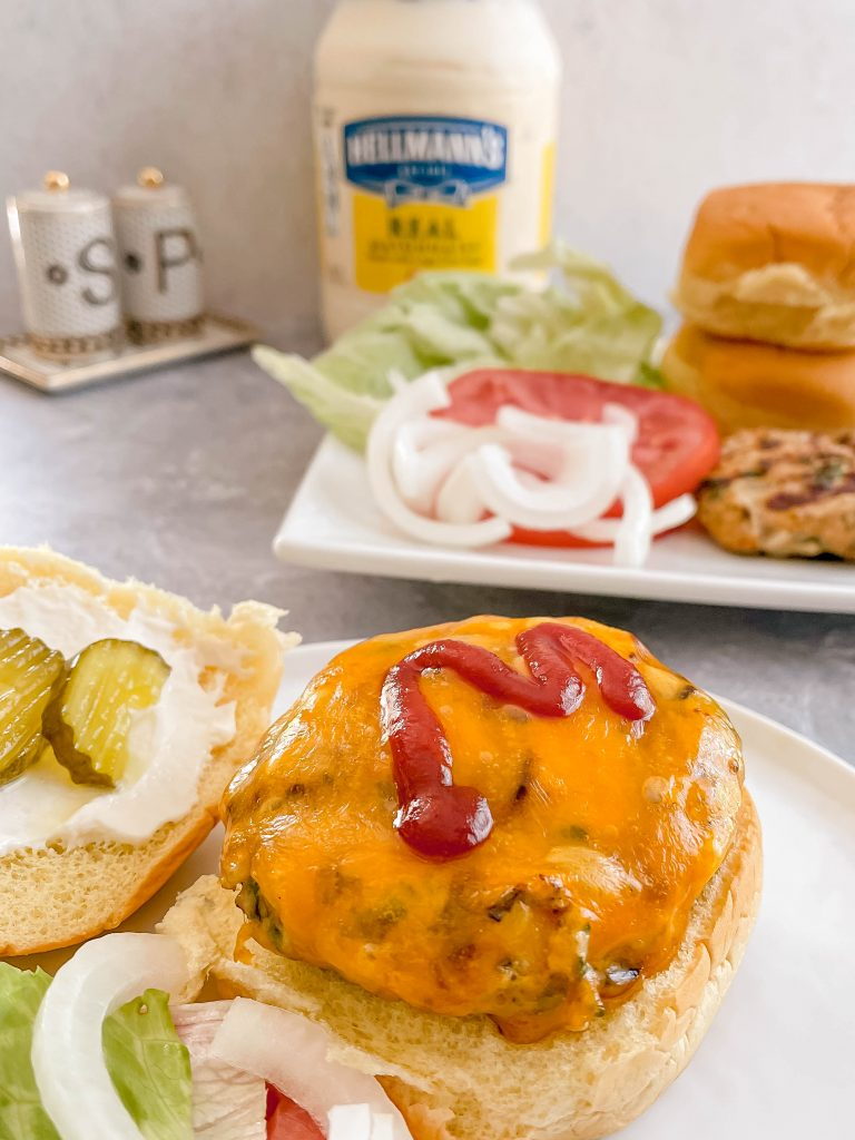 A juicy, cheesy burger up front with toppings, buns, and a jar of mayonaise in the back.