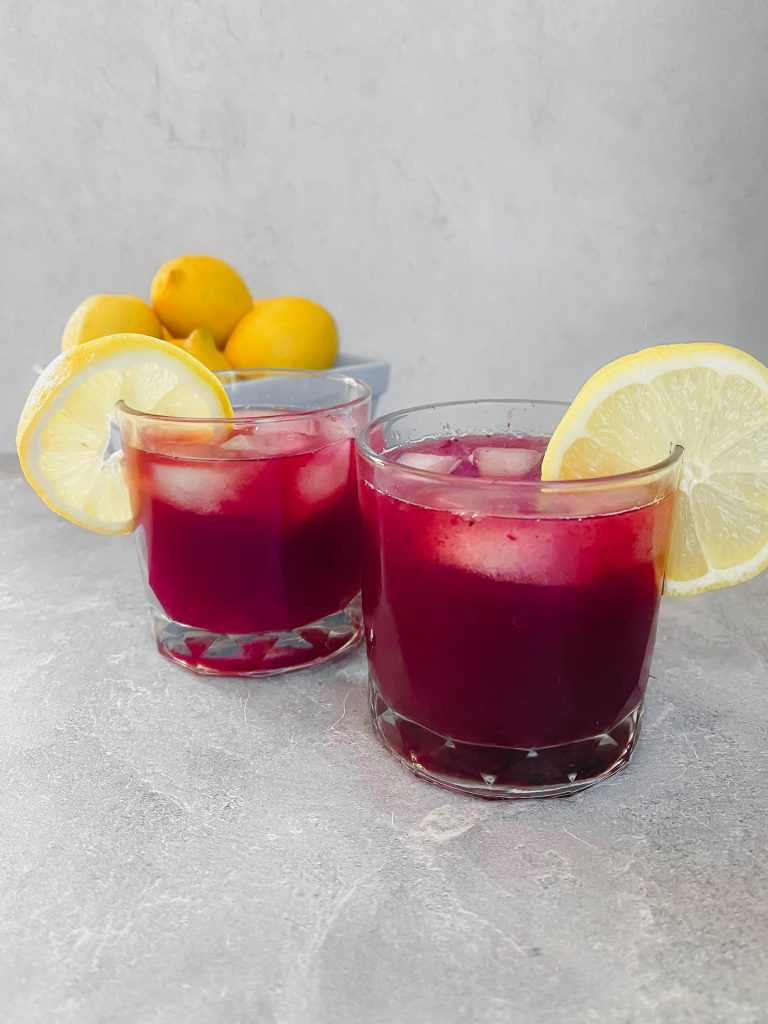 Two rocks glasses with a berry-colored drink, two lemon slices, and a carton of fresh lemons in the background.