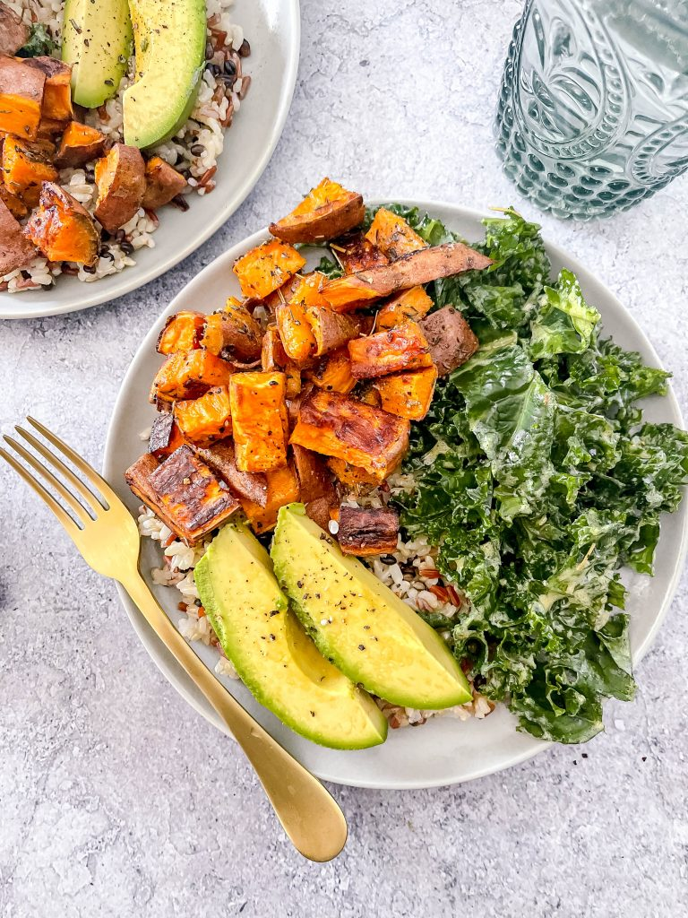 A bowl with brown rice, topped with roasted sweet potatoes, massaged kale, and vibrant avocado.