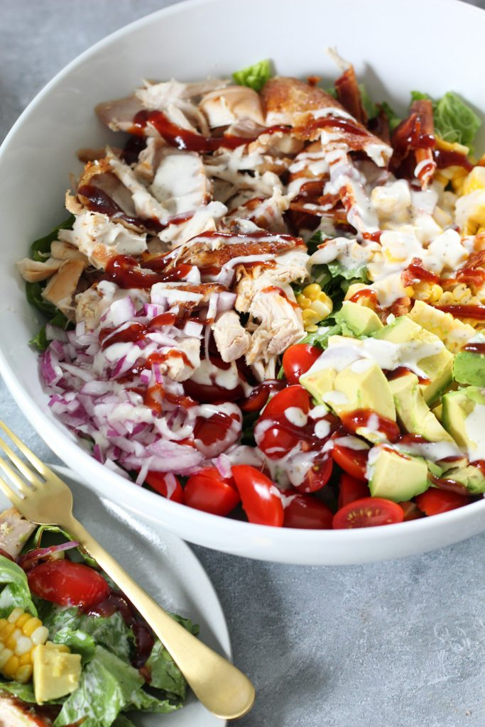 A large white bowl with a bright salad consisting or lettuce, avocado, tomatoes, corn, red onion, chicken, bbq sauce and ranch!
