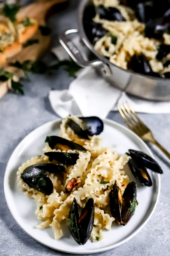Pasta on white plate with mussels