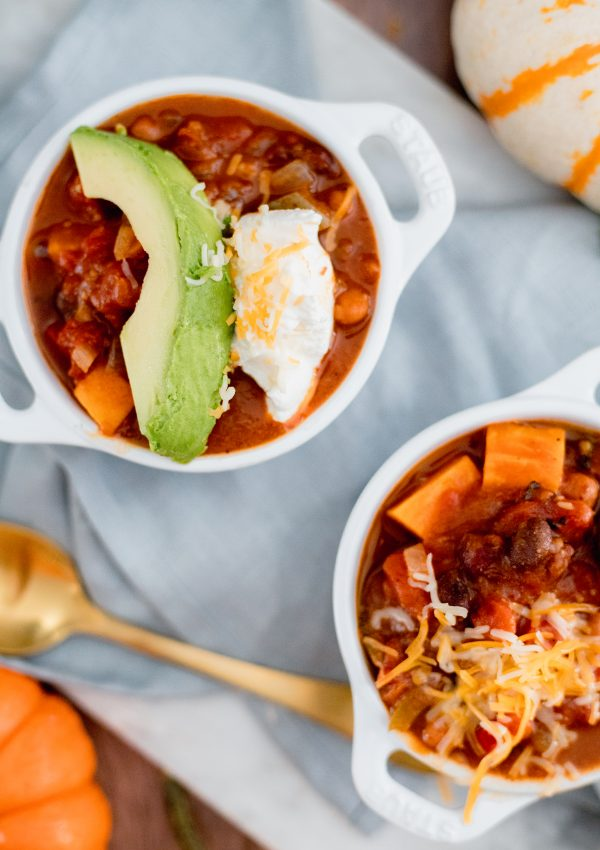 Two white bowls with chili on a gray napkin surrounded by pumpkins and a gold spoon