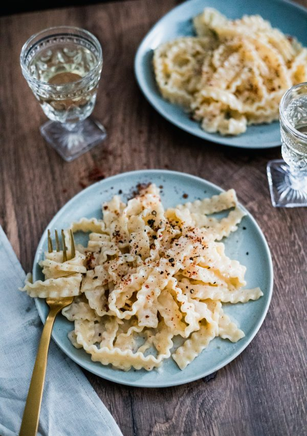 A blue plate on a wooden table with long pasta topped with pink peppercorns. Another plate of pasta in the background, two crystal wine glasses with white wine, and a golden fork.
